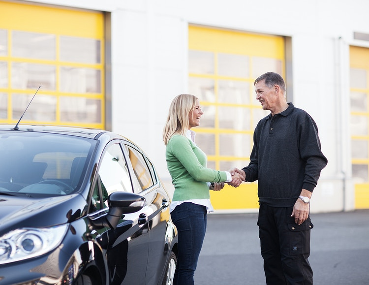 To personer håndhilser foran bil
